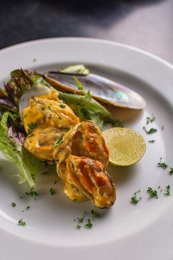 Pan fried mussels with creamy paprika sauce served on a bed of lettuce